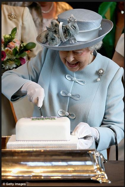 Her Majesty  cuts the cake.
