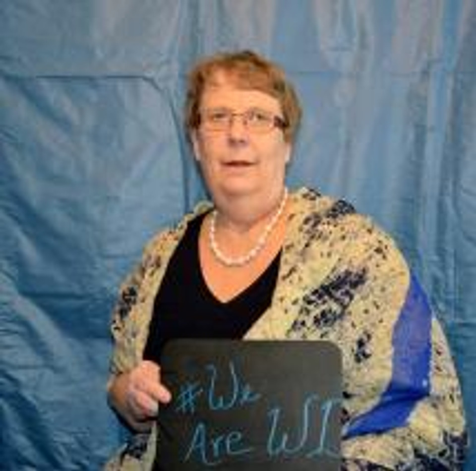 """President Linda Hoy holding a sign that reads """"#We are WI"""""""