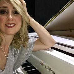 Female pianist and white grand piano