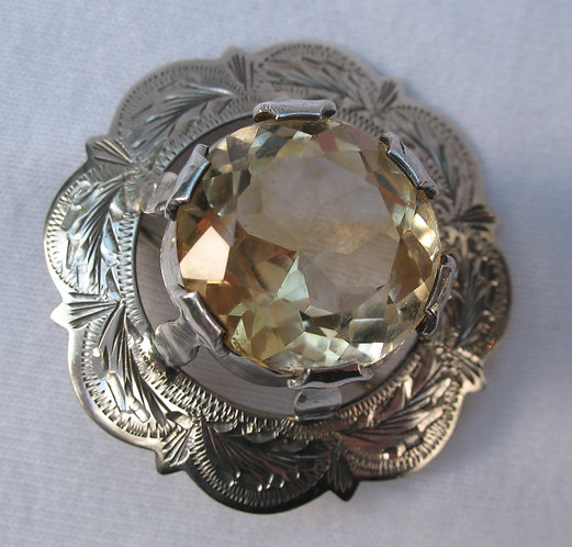 A silver brooch set with a citrine.