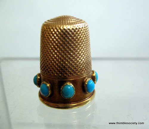Gold thimble set with torquoise coloured stones L10