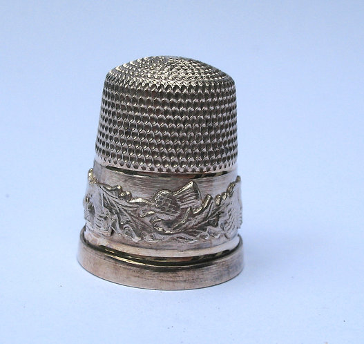 Thimble, silver with thistle decoration.