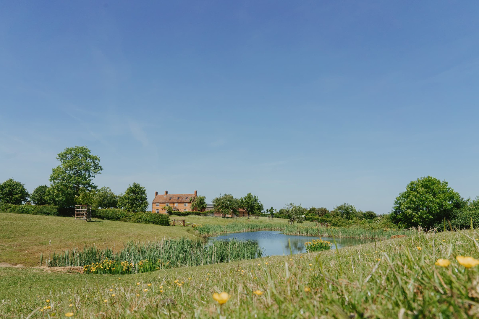 House and pond Primrose Hill Farm Wedding Venue with view of the cotswolds