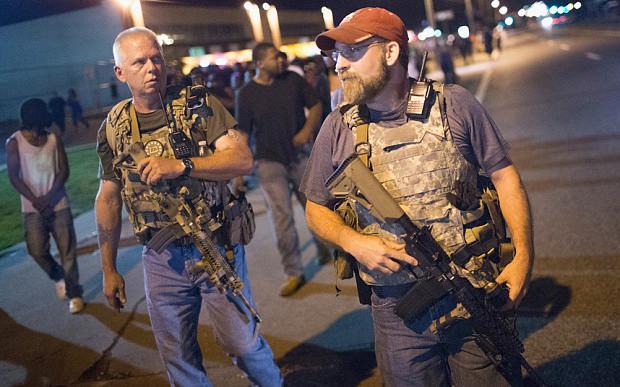"""De Grupp """"Oath Keepers"""" - deen aus Zivilisten besteet - patrouilléiert gären mat hiren schwéiren Waffen."""