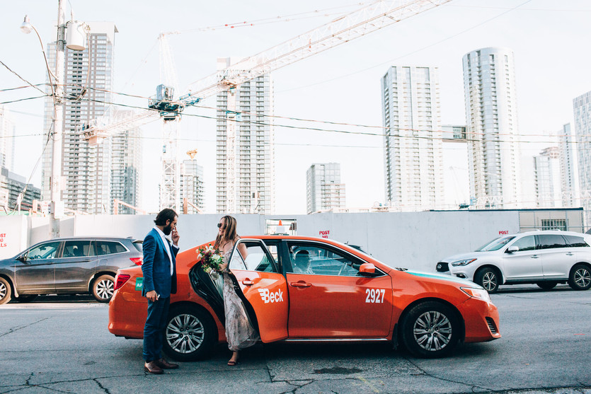 Bride and groom getting out of a taxi