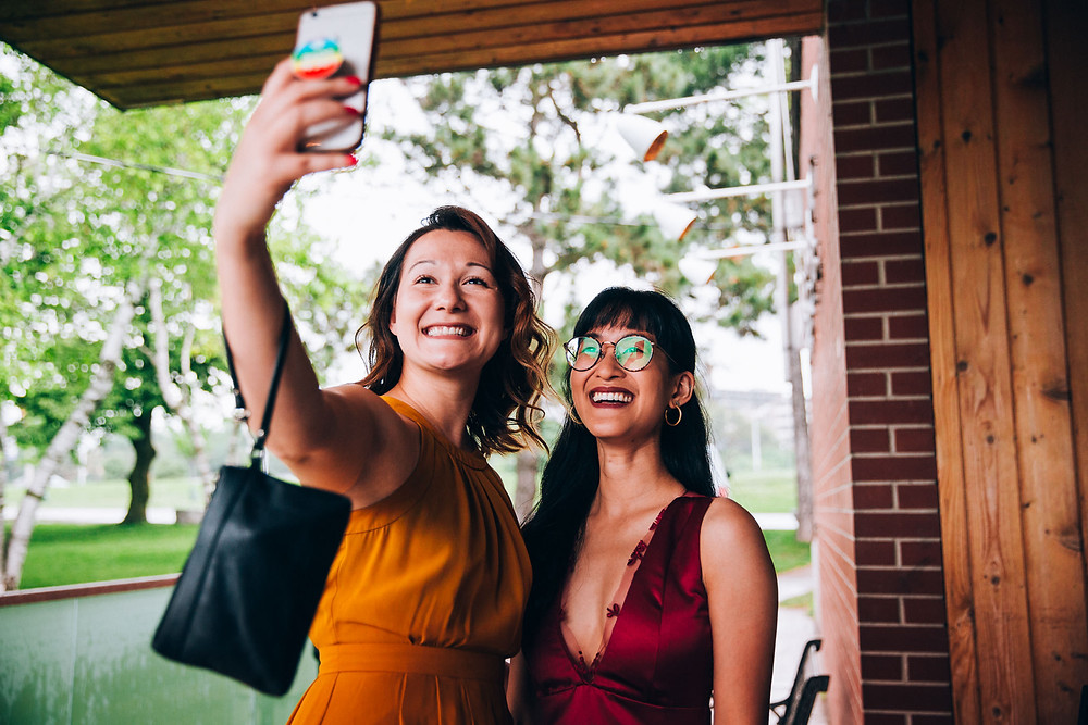 bride and friend taking a selfie at a wedding