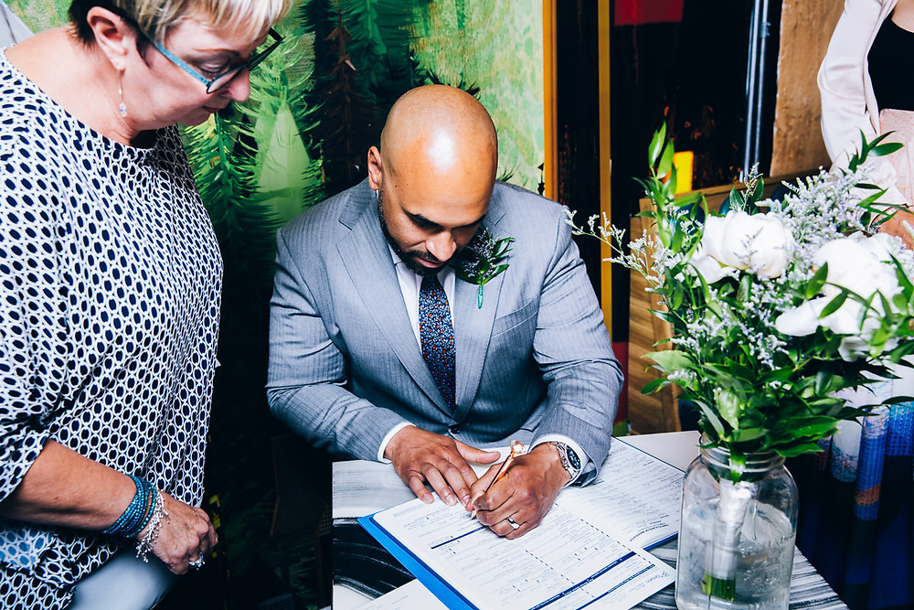 groom signing marriage documents