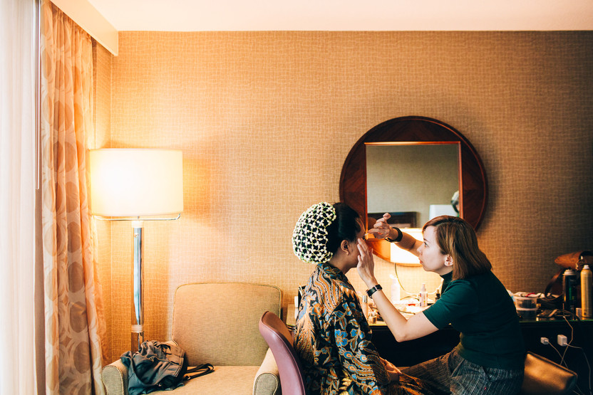 bride getting her makeup done before the wedding in a hotel room