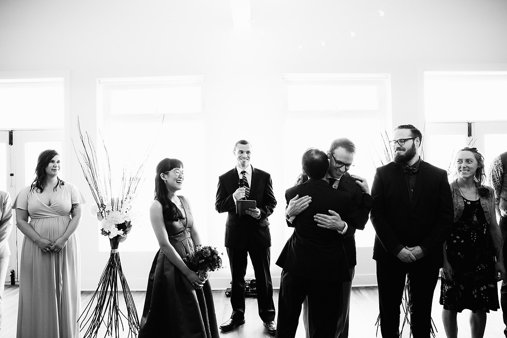 groom hugging the father of the bride