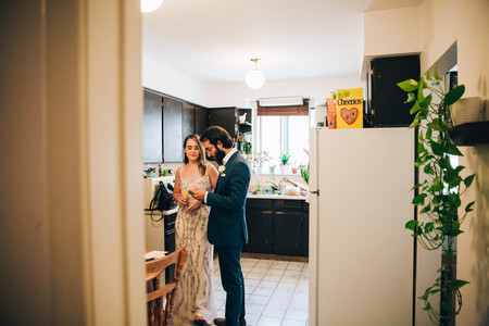 bride and groom in kitchen before wedding