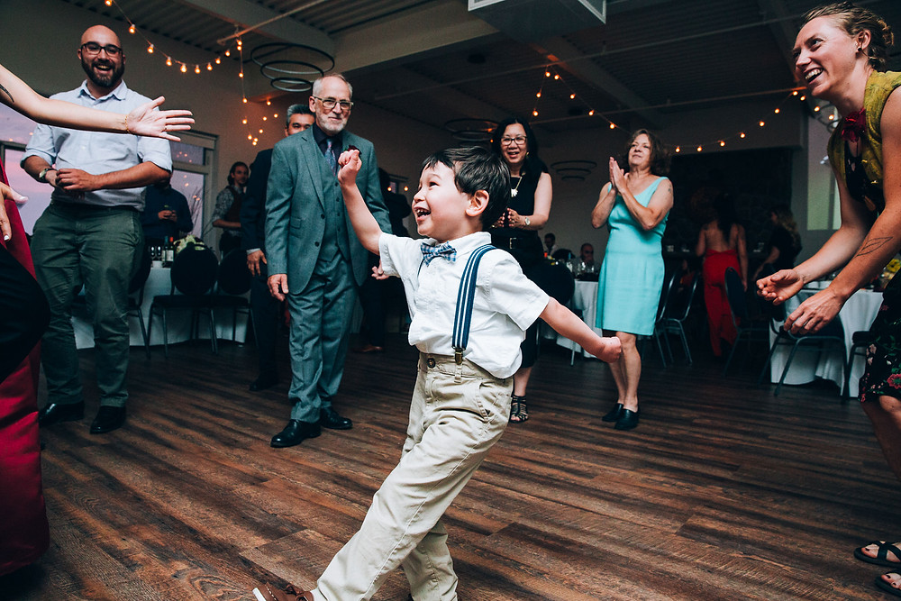 child wearing a bow tie and suspenders dancing