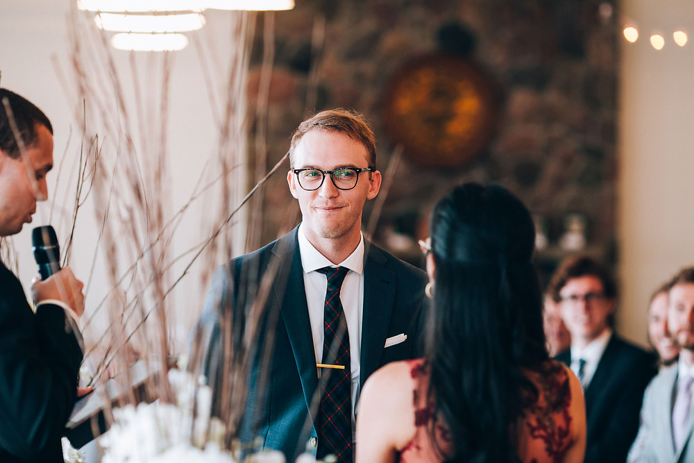 groom smiling at bride during wedding ceremony