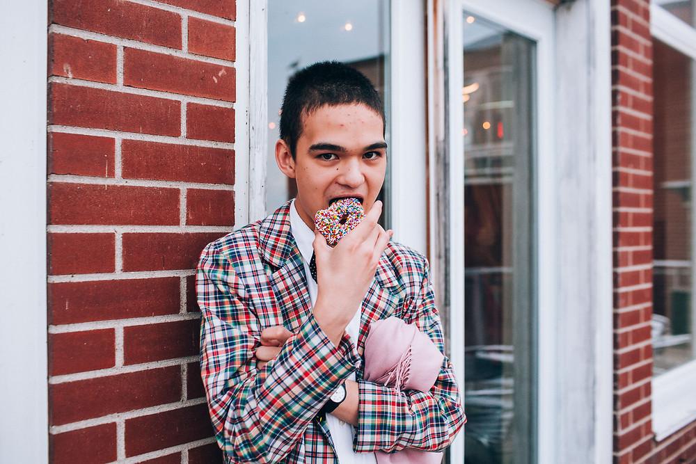 boy in plaid jacket eating a sprinkle donut
