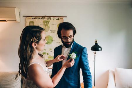 bride pinning corsage on groom