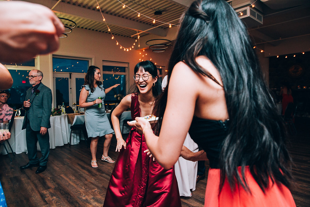 bride in red wedding dress dancing at her reception