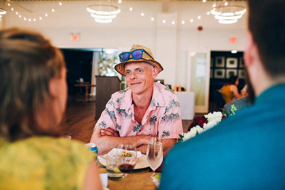 guest at wedding wearing pink hawaiian shirt and straw hat