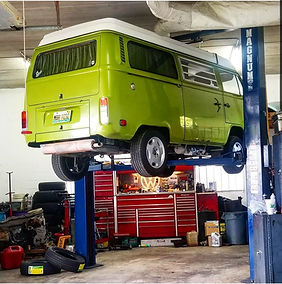 volkswagen bus at the mechanic being serviced by a vintage vw expert
