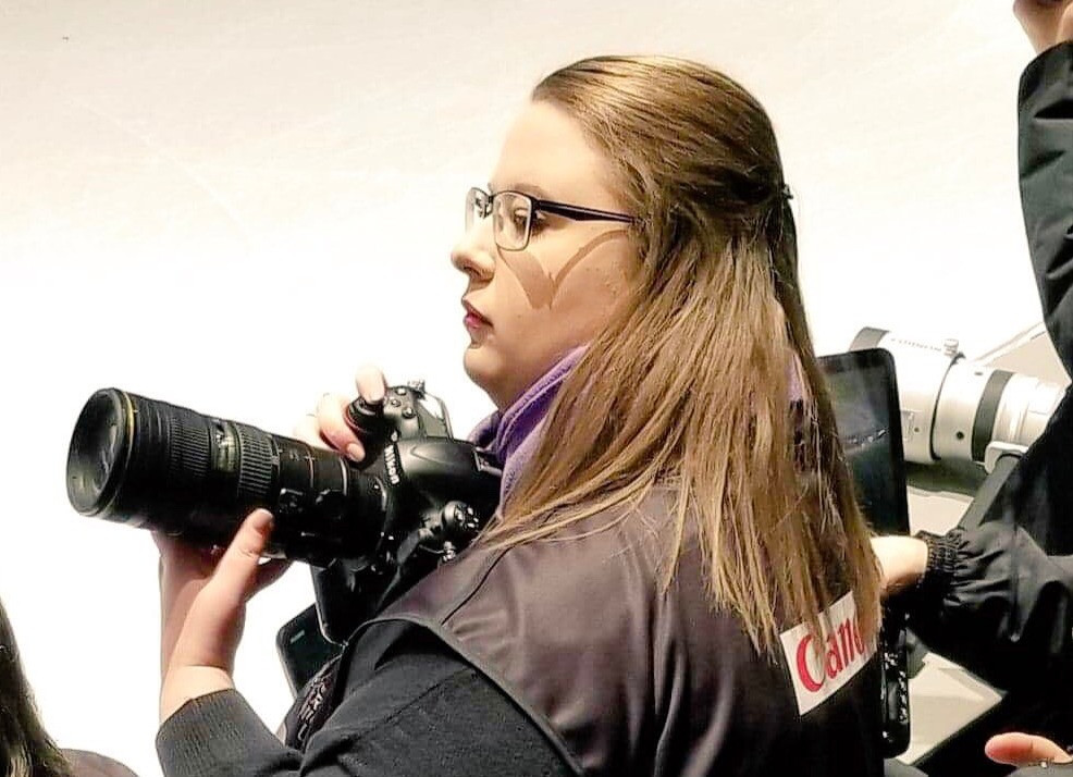 Danielle Earl photographing a figure skating event with her Nikon DSLR camera