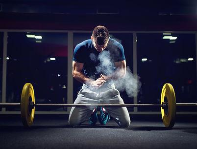 Handsome weightlifter preparing for trai