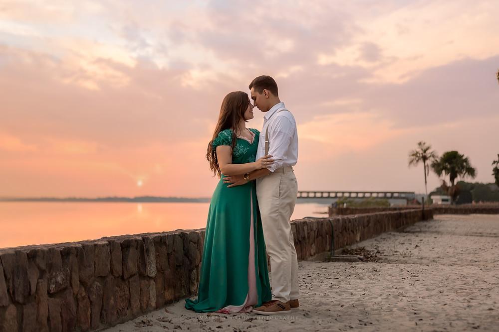 Casal de noivos na praia em um por-do-sol.