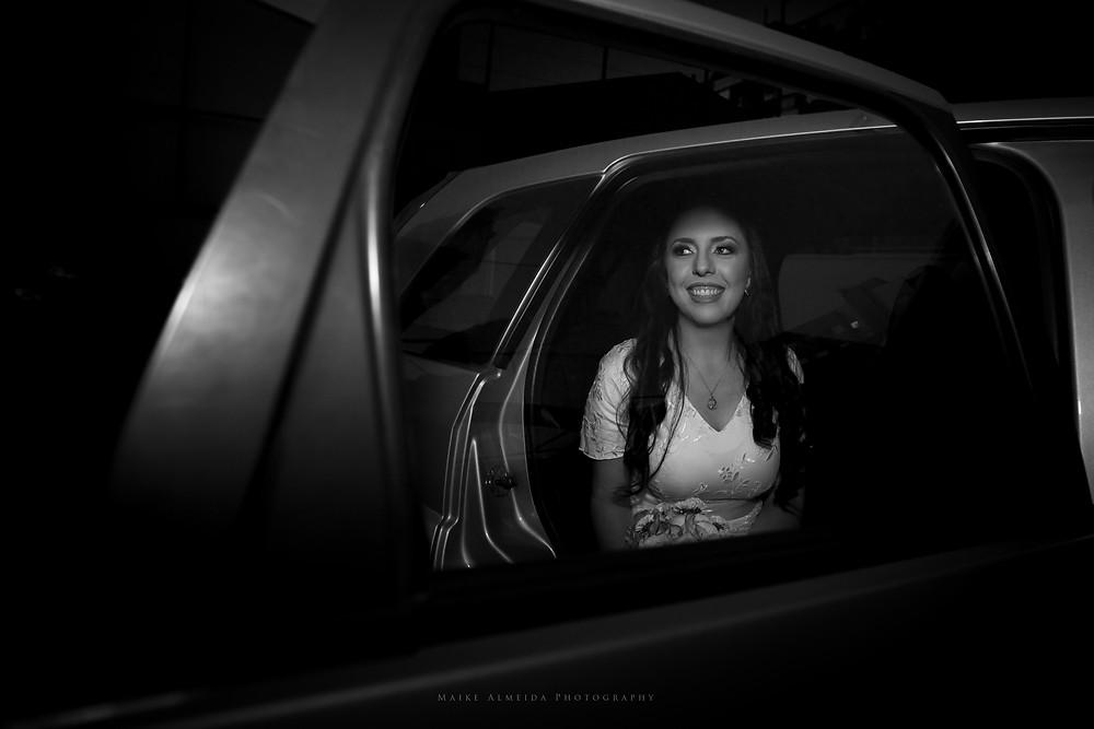 Mulher vestida de noiva saindo do carro. Foto em preto e branco.