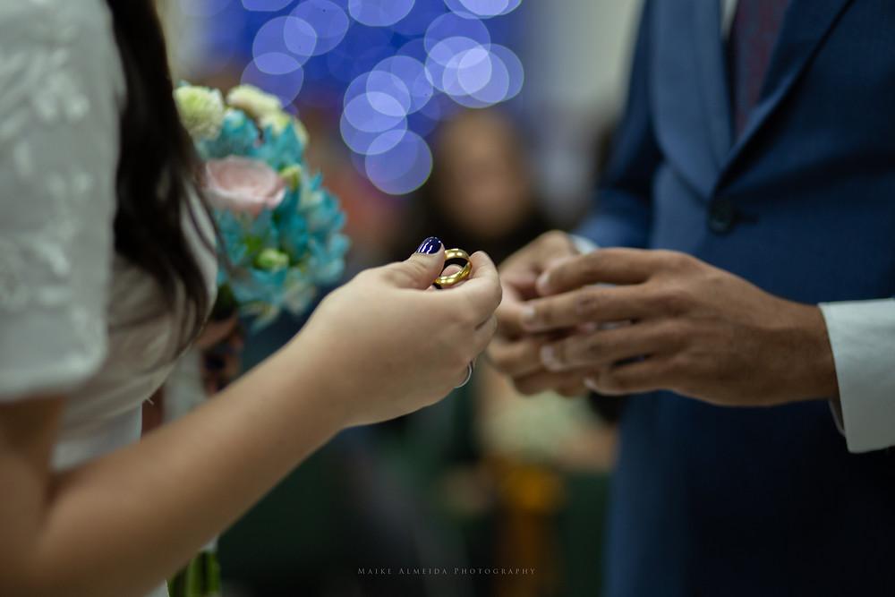 Casal de noivos trocando alianças.