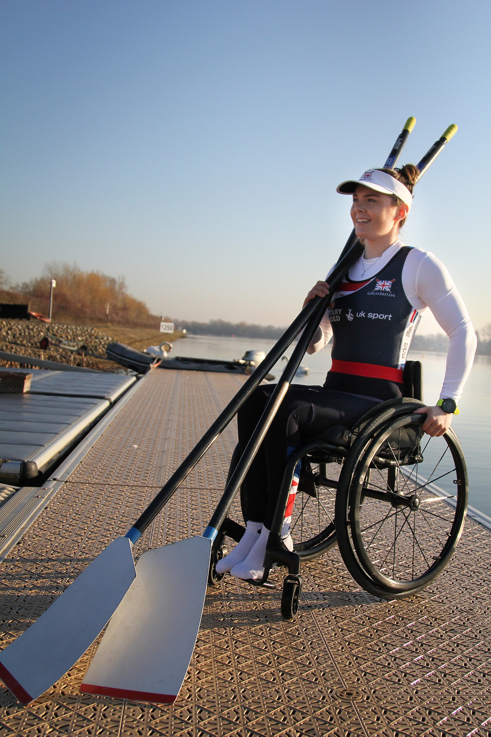 Lauren Rowles by the water with her rowing oars I Parasports World Interview