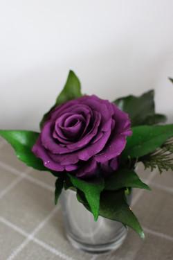 Purple single rose in votive