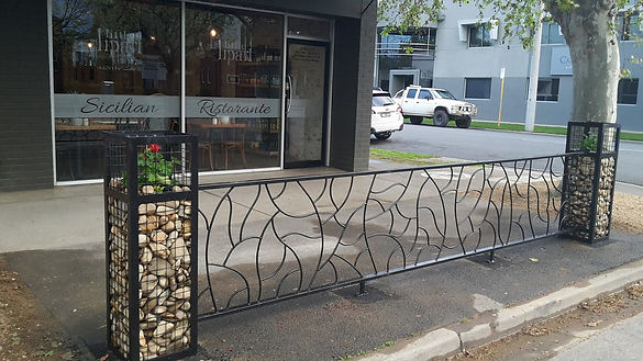 outdoor dining barrier, made from metal,  gabion stone filled pillars with planters for cafes
