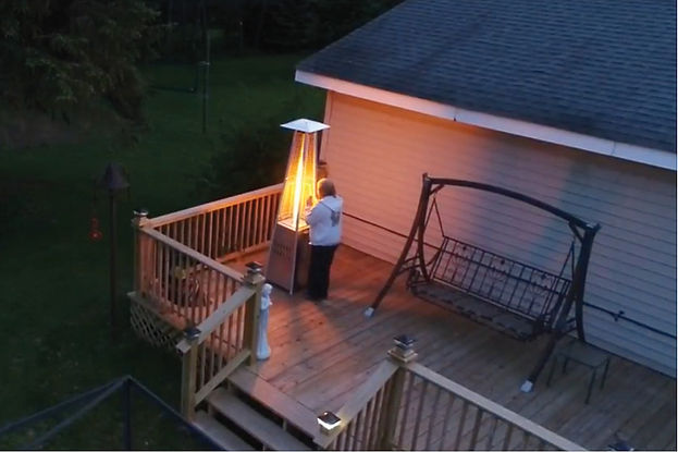An aerial view, shot from a drone, picturing a person on their porch warming their hands at a heat lamp.