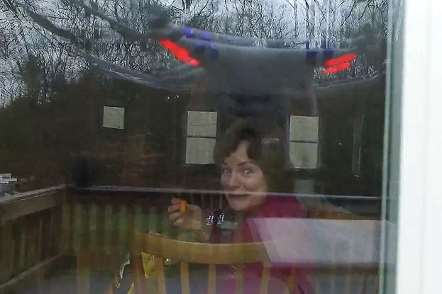 An aerial view, shot from a drone, picturing a woman eating behind a glass door. She is looking at the camera.