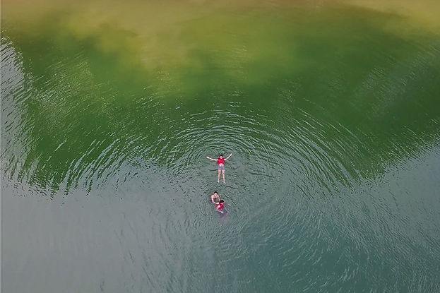 An aerial view, shot from a drone, picturing three peole wearing red shirts swimming in alarge green lake.