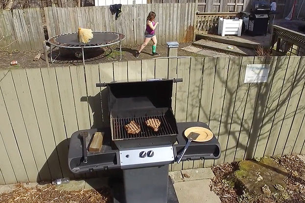 An aerial view, shot from a drone, picturing a barbecue grill with a fence behin it. On the other side of the fence, a young woan in a purple tank top is walking away a trampoline.