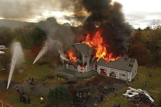 An aerial view, shot from a drone, picturing a two story house on fire.