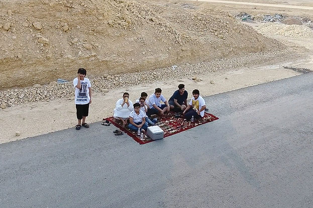 An aerial view, shot from a drone, picturing a group of people on a red rug by rocksand rubble sitting next to the road.