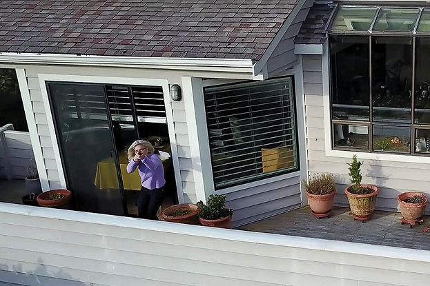 An aerial view, shot from a drone, picturing a woman in a purple sweater on her back porch pointing a gun at the camera.