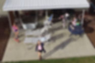 An aerial view, shot from a drone, picturing a young woman in a pink shirt on her back patio staring up at the camera.