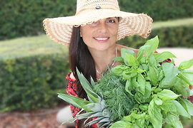 Vasiliki Holding Herbs and Other Plants In The Garden