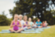 Front view of children doing yoga in the