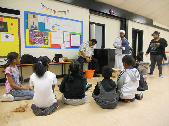 Allen Vincatassin demonstrates the traditional way to grate coconuts to young Chagossians in Crawley