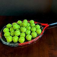 Tennis balls on racquet.jpeg