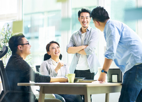 group-of-four-happy-young-asian-corporate-people-teammates-meeting-discussing-business-in