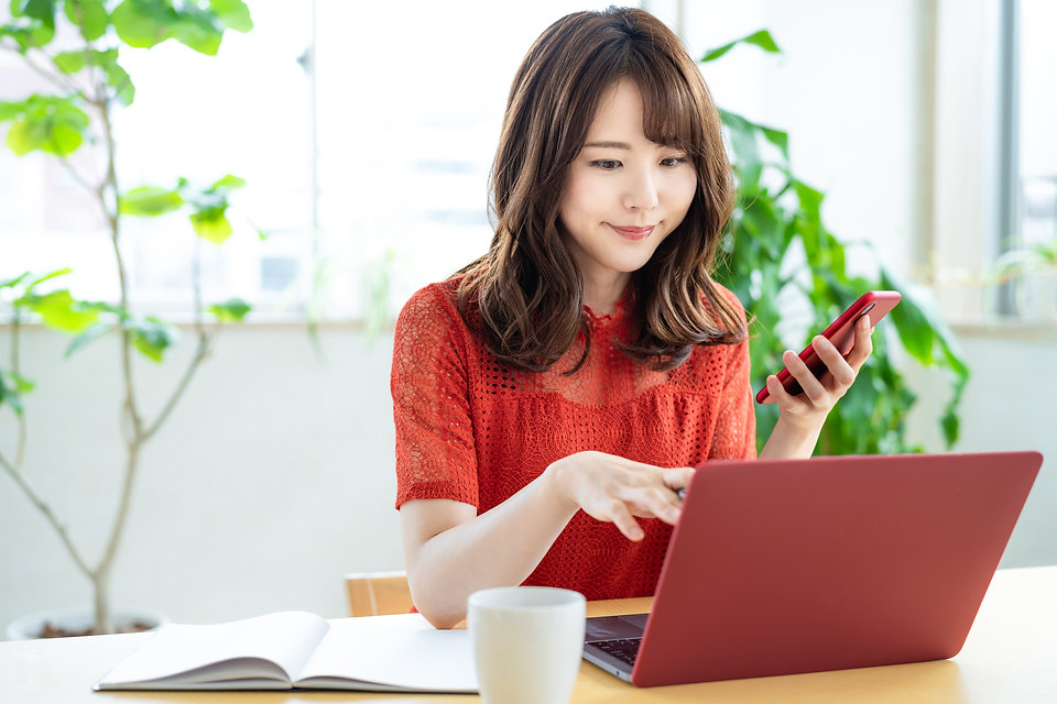 Attractive asian woman using a laptop PC and a smart phone..jpg