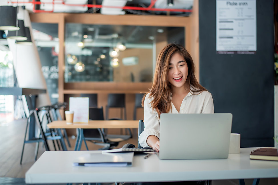 Happy young asian businesswoman sitting on her workplace in the office. Young woman workin