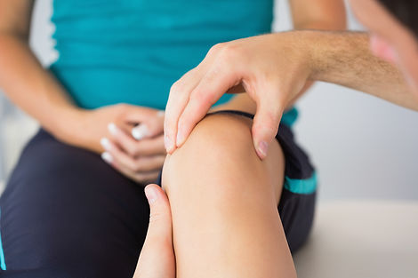 Physiotherapist controlling patients knee in bright office.jpg
