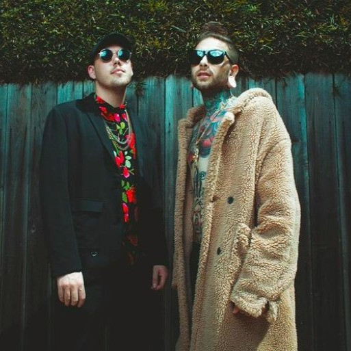 Josh Miller and Tom Barber stood in front of a dark blue fence looking cool