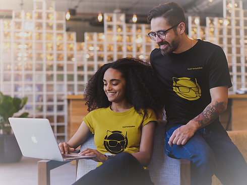smiling-coworkers-wearing-t-shirts-mockup-while-watching-a-laptop-a20430_edited.png