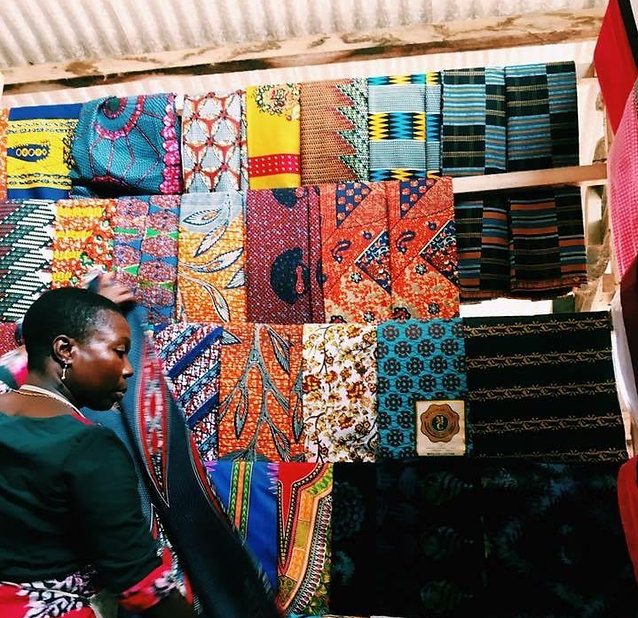 Seamstress from Ghana hanging African wax prints in a store