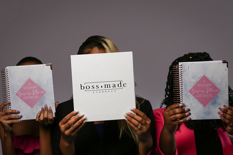 Three women hold our business planner and packaging.