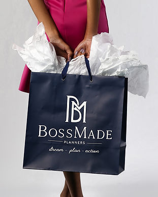 Woman holding a Boss Made Planners gift bag.